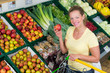 attractive woman with an apple in a grocery