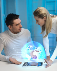 futuristic man and woman with globe hologram