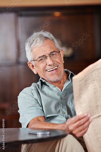 Senior man with glasses reading newspaper