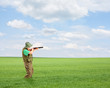 Male hunter shooting with a rifle outside in a field