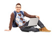 Smiling handsome guy sitting on a floor with laptop and looking