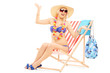 Young happy female with a hat posing on a beach chair