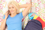 Blond female student lying in bed and talking on a phone