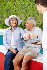 Two senior people relaxing at pool with cocktails
