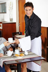 Smiling waiter in coffee shop