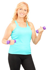 Mature smiling woman lifting up dumbbells