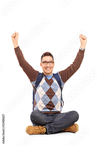 Handsome young man sitting on a floor with raised hands gesturin