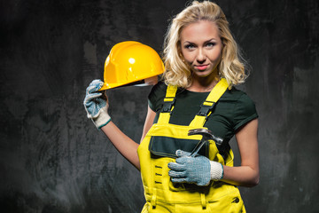 Builder woman with protective helmet posing against grey wall