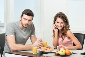 couple having breakfast, girl talking on the phone