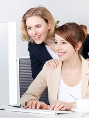 Two business women work together in the office
