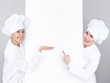 Female cooks show white blackboard with copyspace