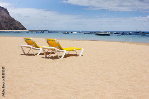 yellow lounge chairs on the sea beach