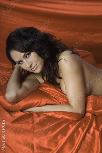 woman on red satin sheets