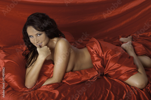 canvas print picture woman on red satin sheets