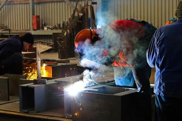 Welders work in the factory floor