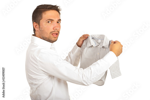 Shocked man holding shrunk shirt