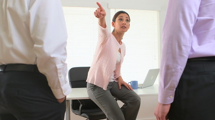 Angry female executive in a meeting with employees