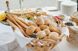 buffet table with basket of bread in foreground