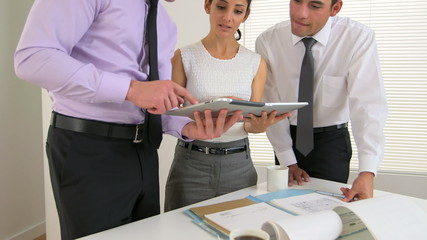 Closeup of three business people using tablets