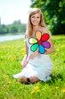 Smiling woman with a rainbow flower outdoors