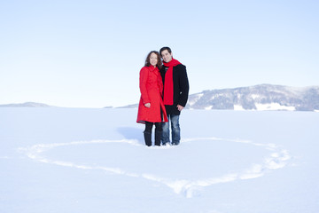 Happy young couple in winter with snow heart