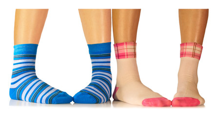 women's and children's legs in colorful striped socks isolated o
