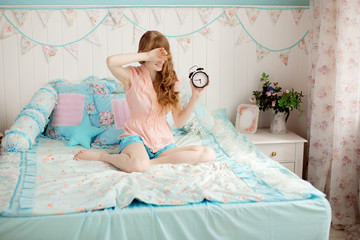 Cute young girl in nice children's bedroom with alarm clock