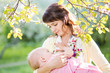 young mother breast feeding her baby girl at sunny day