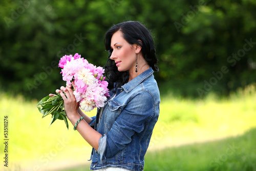 Beautiful woman in a park with bouquet