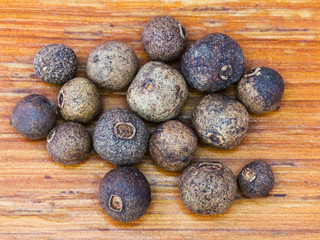 allspice seeds on wooden board