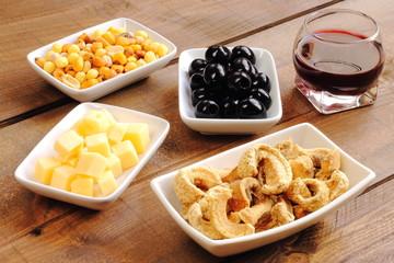 Aperitivo con queso, aceitunas, frutos secos, torreznos y vino