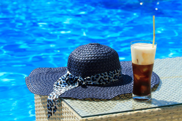Ice coffee Fredo against blue clear water of the swimming pool