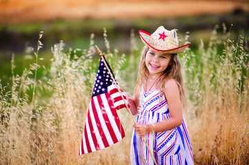 Happy adorable little girl smiling and waving American flag outs
