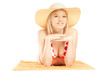 Smiling beautiful female with hat lying on a beach towel