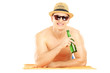 Smiling guy with hat lying on a beach towel and drinking cold be