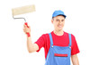 Smiling painter in a uniform holding a roller