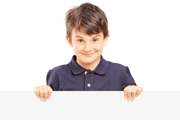 Little smiling boy standing behind a blank panel
