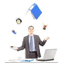 Young businessman in a suit juggling with office supplies in his