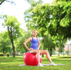 Young female athlete sitting on a  pilates ball in park