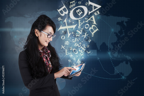 Businesswoman communicating with touchpad on blue background