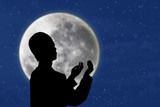 Silhouette of muslim man praying under blue moon