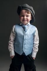 Little boy in cap and blue vest