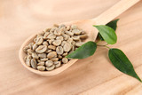 Fototapety Green coffee beans in spoon and leaves on wooden background