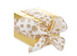 Golden gift wrapped present with dotted bow over white