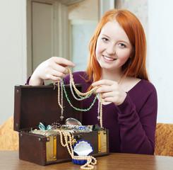 red-headed girl looks jewelry