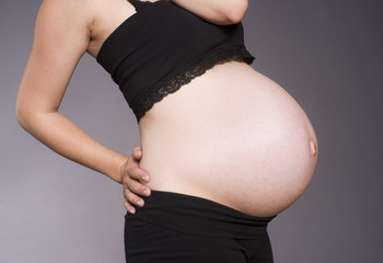 Pregnant Woman Torso Standing Bending Black Gray Background