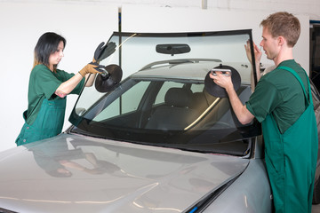 Glazier replacing windshield