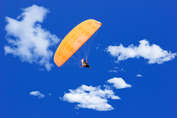 paraglider flying in a blue sunny sky with clouds