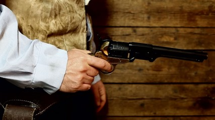 Gunslinger pulls out the gun on wooden background