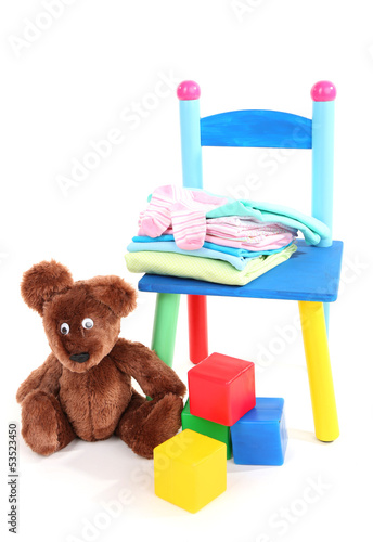 Small and colorful chair with baby clothes isolated on white